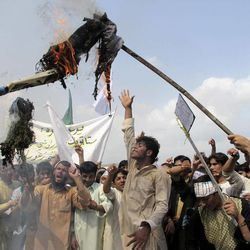 """Afghans burn an effigy of U.S. President Barack Obama during a protest in Khost, south-east of Kabul, Afghanistan, Saturday, Sept. 15, 2012. A few hundred of university students protested against an anti-Islam film which depicts the Prophet Muhammad as a fraud, a womanizer and a madman, in Khost, shouting """"death to America."""""""