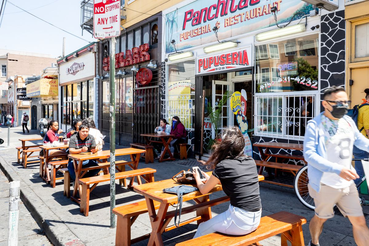 Diners seated at sidewalk picnic tables at Panchita's #2 in the Mission