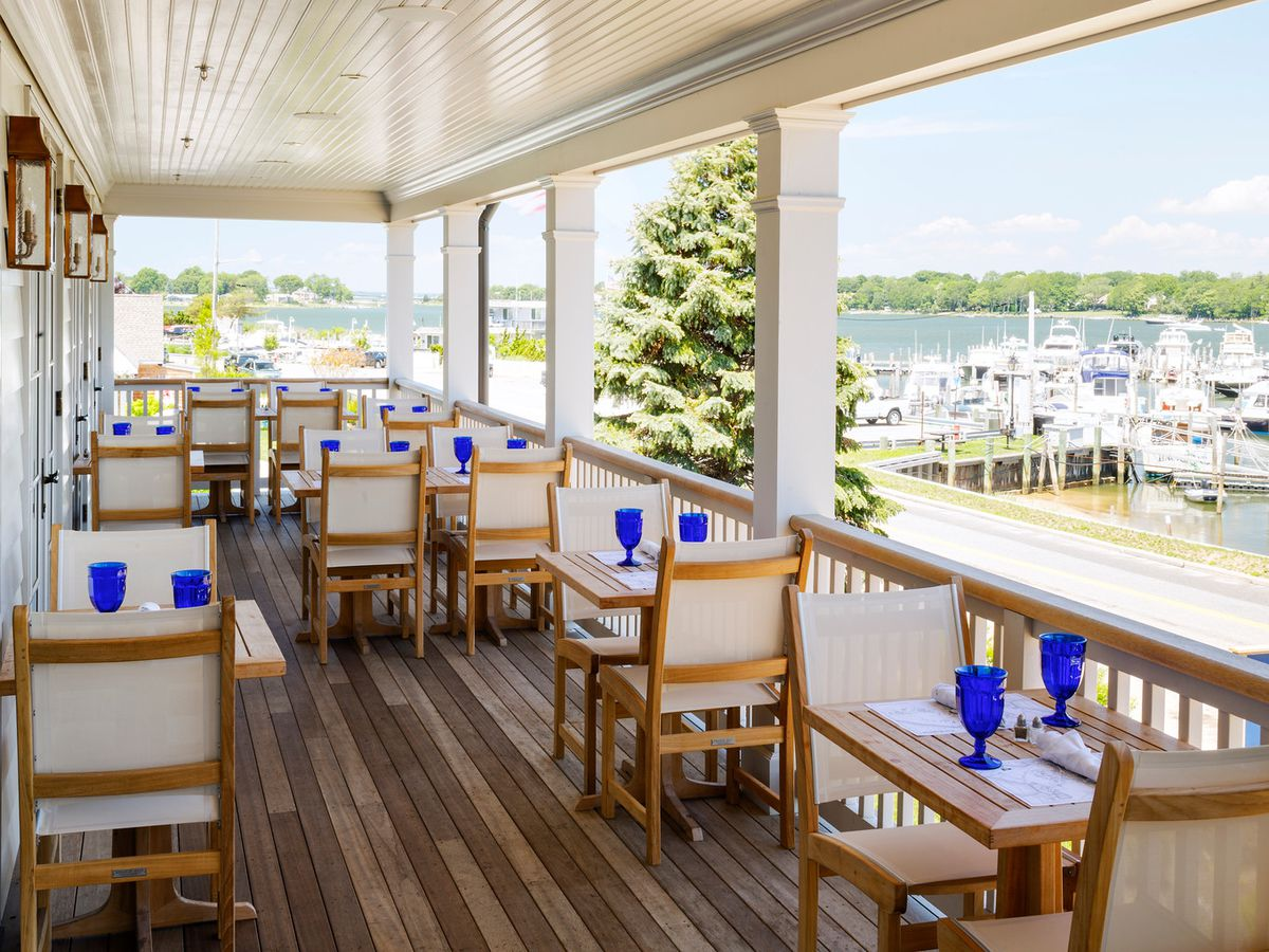 Tables and chairs set up on a high patio overlooking a harbor on a sunny day