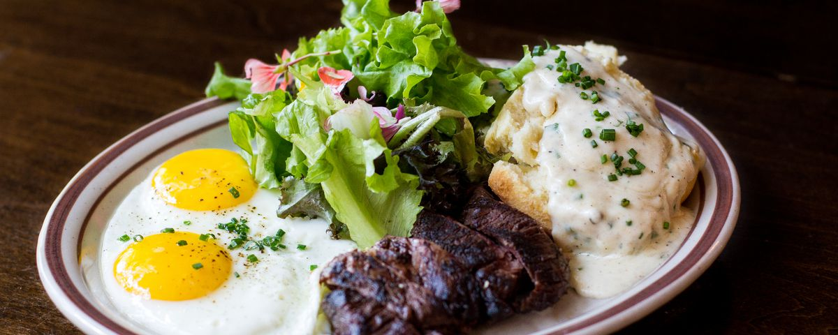 A white plate of two sunny side up eggs, a small streak filet, a biscuit with gravy, and a small salad