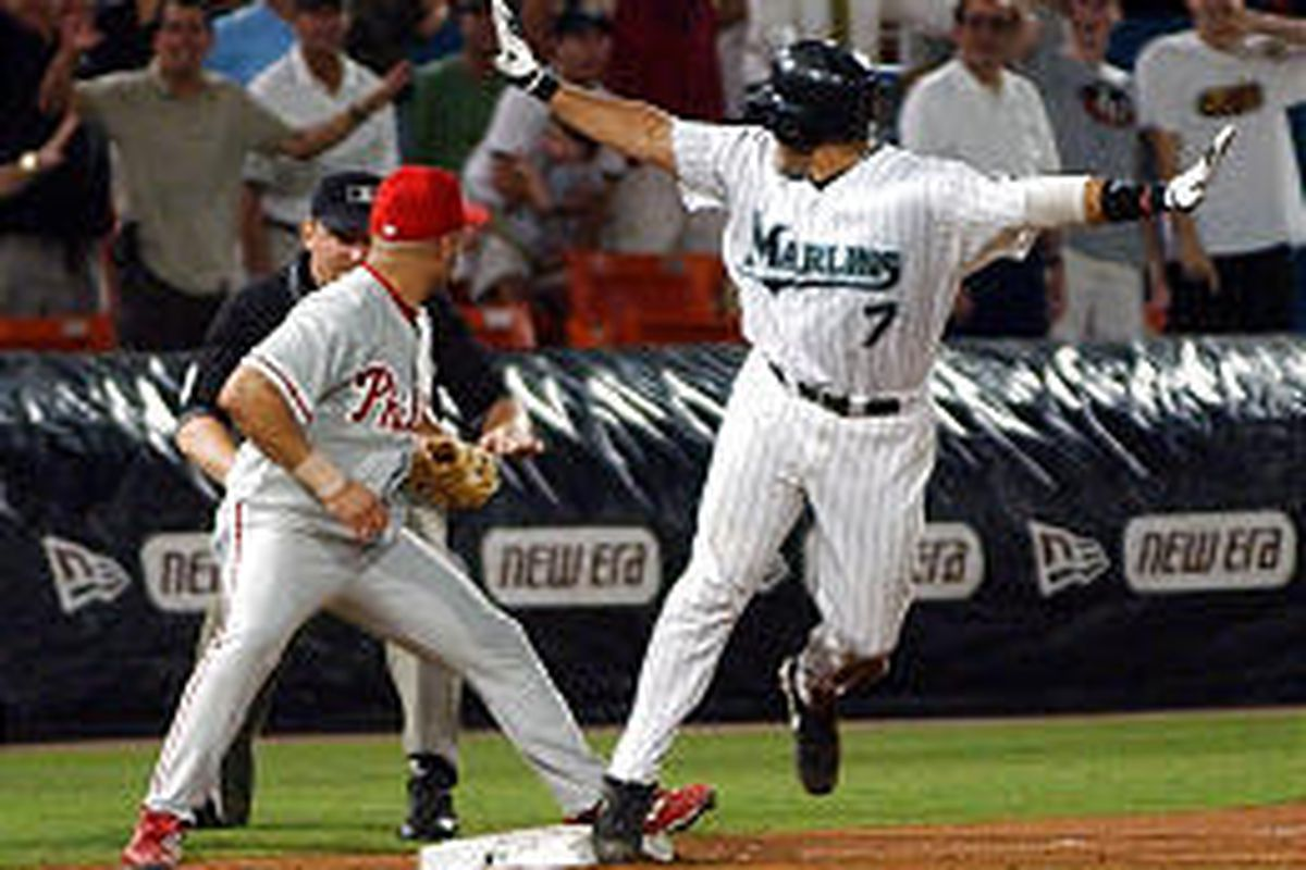 Florida Marlins' Ivan Rodriguez, right, makes the safe sign as he looks at the umpire for the call in the win.