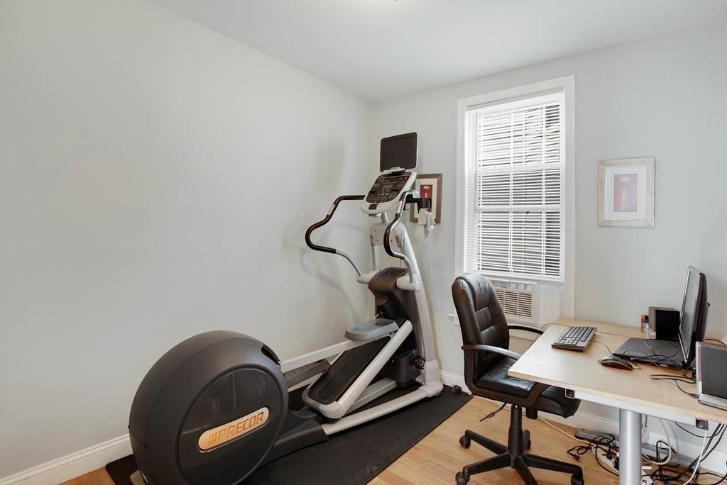 A small room with a window, a stair machine, and a desk with a chair.