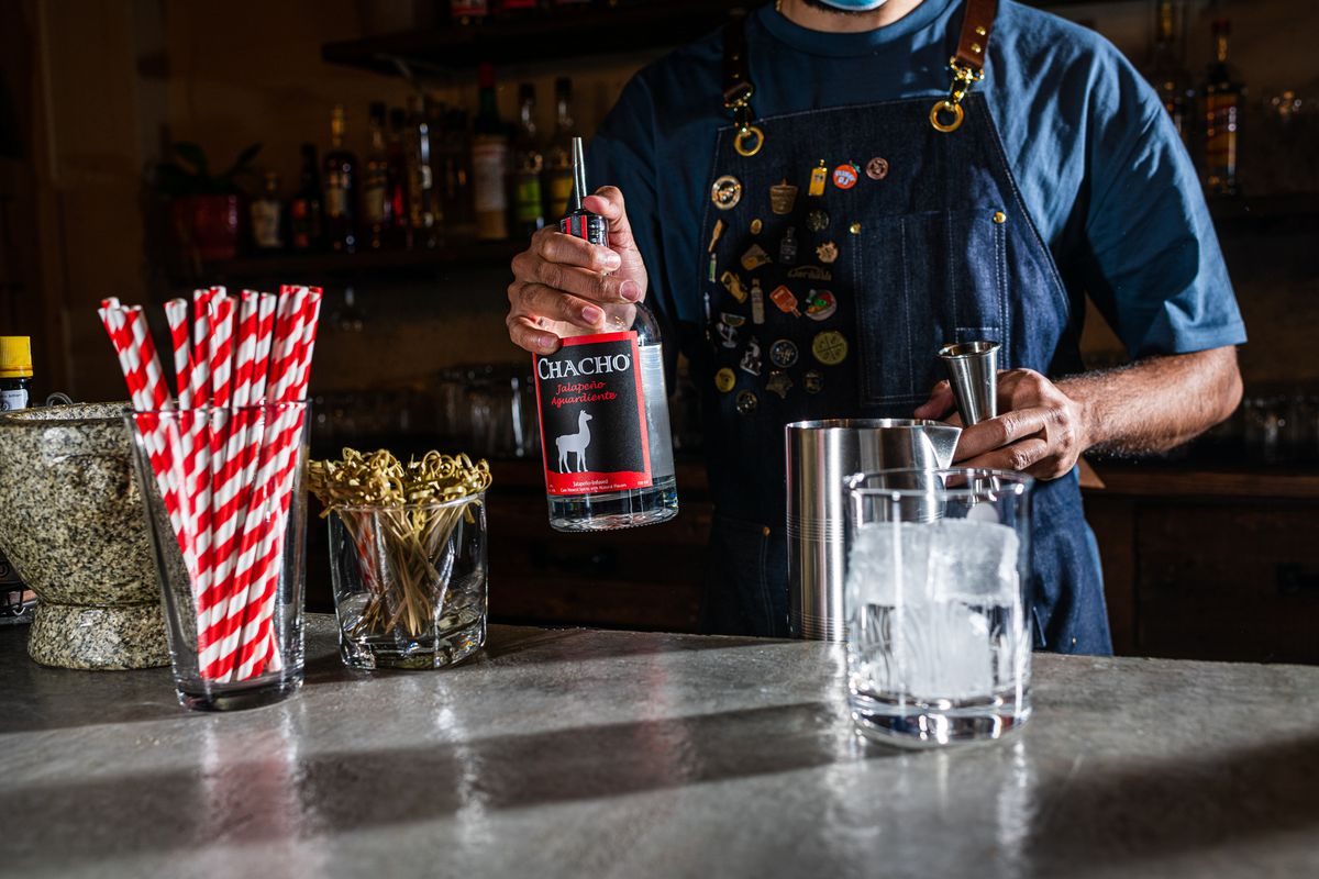 A bartender holds a bottle of Chacho topped with a pouring spout