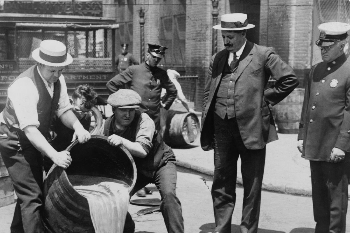 Police oversee the confiscation and destruction of liquor during Prohibition.