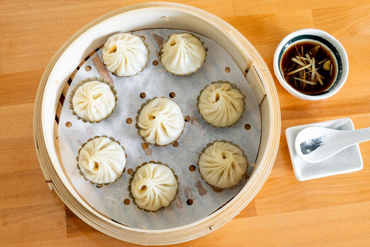 A steamer full of xiao long bao, with vinegar and ginger dip on the side