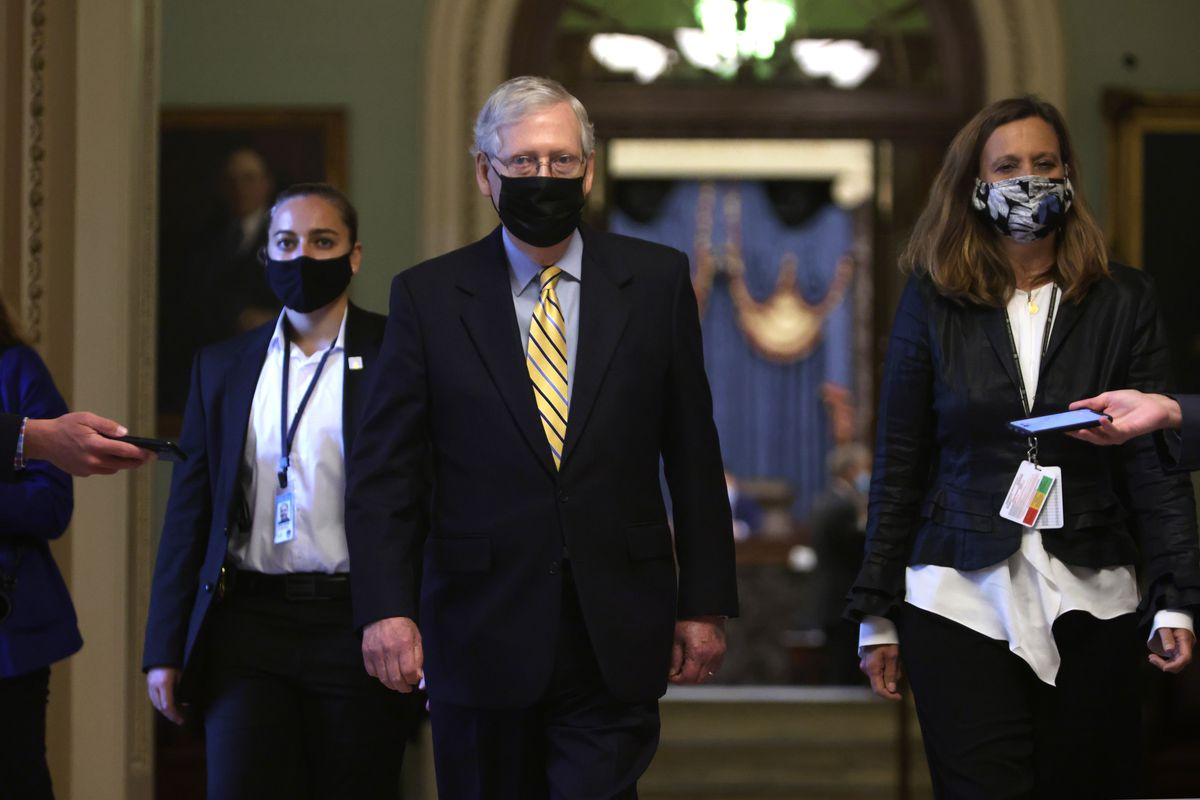 Mitch McConnell walking and wearing a mask.