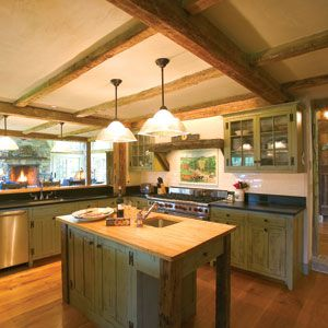 <p>The interior shows off much of the original structure's framework, including old loft beams in the kitchen. The fireplace in the adjacent great room was added in the conversion, mirroring one that already existed in the sleeping quarters.</p>