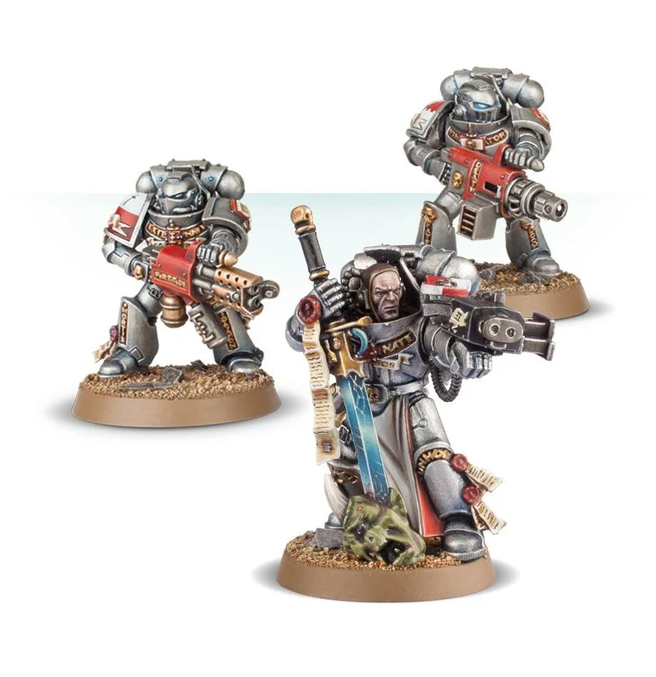 Three space marines in silver armor with gold accents stand ready for battle.