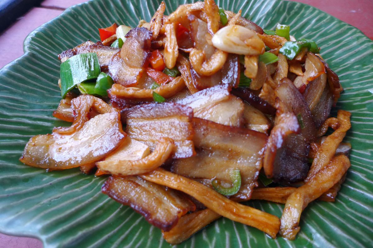 A stir fry of bacon swatches, green onions, and green chiles on a green plate.