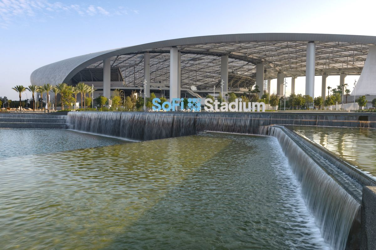 An exterior shot of the new NFL Los Angeles stadium with sweeping steel and a water feature at front.