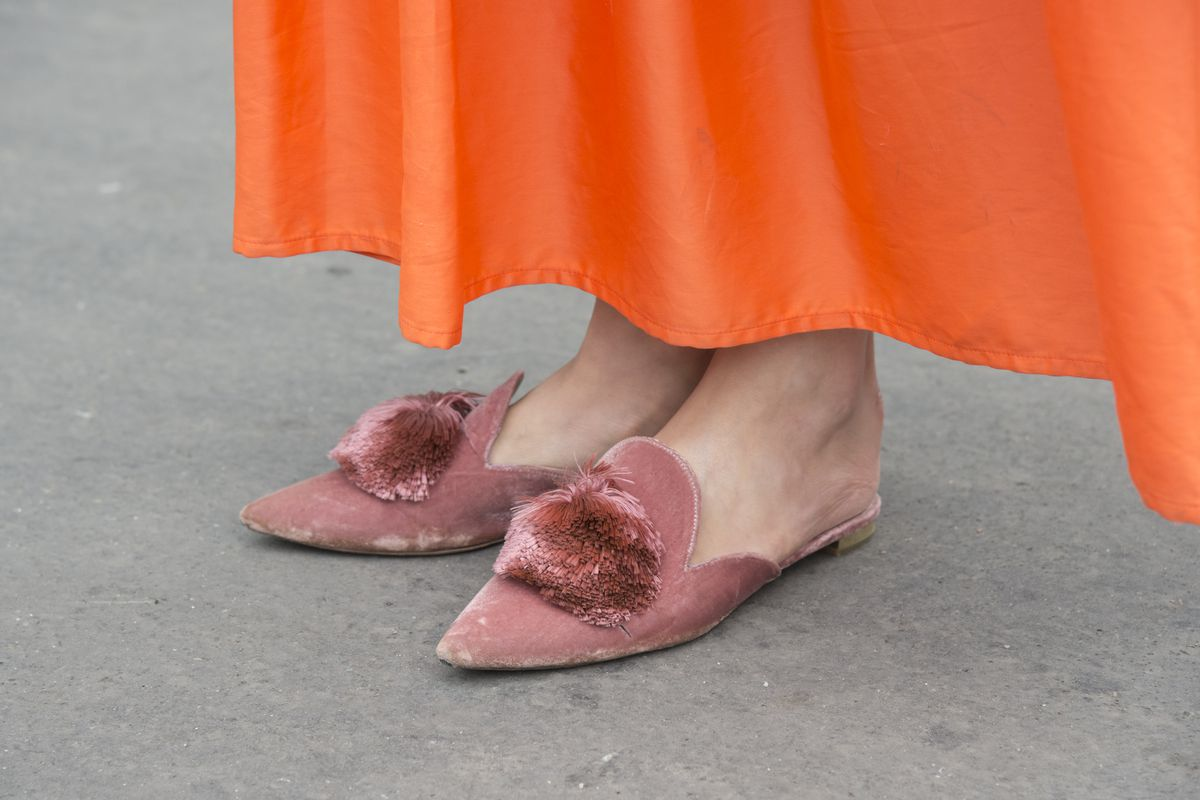 A pair of feet wearing pink velvet slippers with pom poms on the toe.