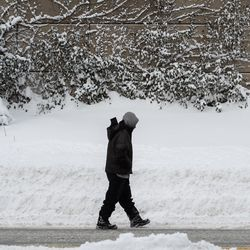 A pedestrian walks in the Edgewater neighborhood, Tuesday morning, Feb. 16, 2021, after a snowstorm dumped over a foot of snow in Chicago starting Sunday night. Snow is expected to continue to fall until Tuesday night.