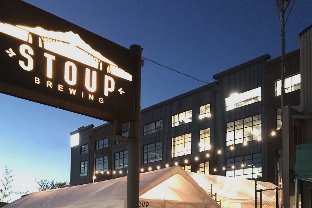 The outside of Stoup Brewing at twilight, with the brewery's sign lit up