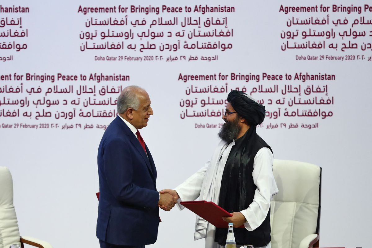 US Special Representative for Afghanistan Reconciliation Zalmay Khalilzad and Taliban co-founder Mullah Abdul Ghani Baradar shake hands after signing a landmark peace agreement during a ceremony in the Qatari capital Doha on February 29, 2020.