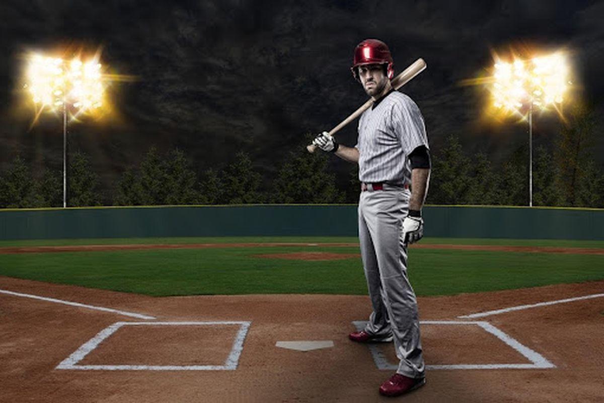 Baseball player poses at home plate in baseball stadium