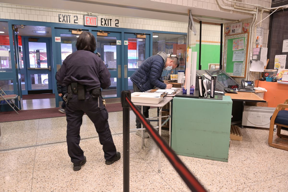 A school security guard watches a parent sign in at the entrance of their school.