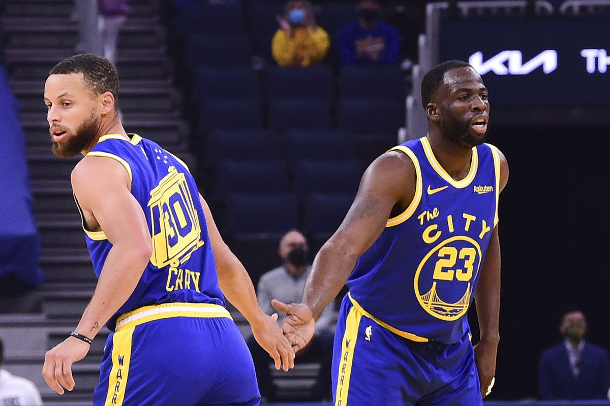 Stephen Curry #30 of the Golden State Warriors high fives Draymond Green #23 of the Golden State Warriors during the game against the Phoenix Suns on May 11, 2021 at Chase Center in San Francisco, California.