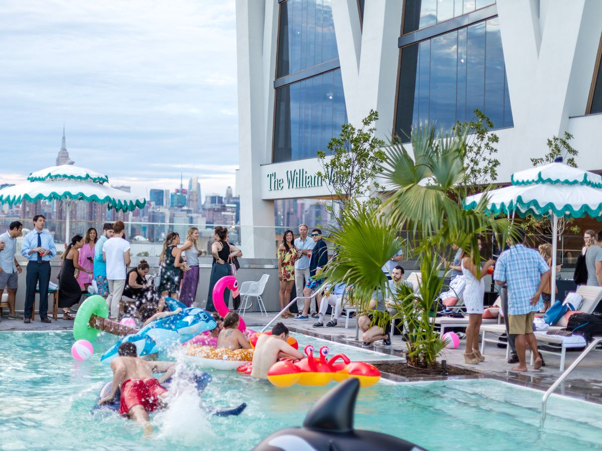 A rooftop swimming pool. There are colorful inner tubes in the pool. There are people in the pool and in the lounge area surrounding the pool.