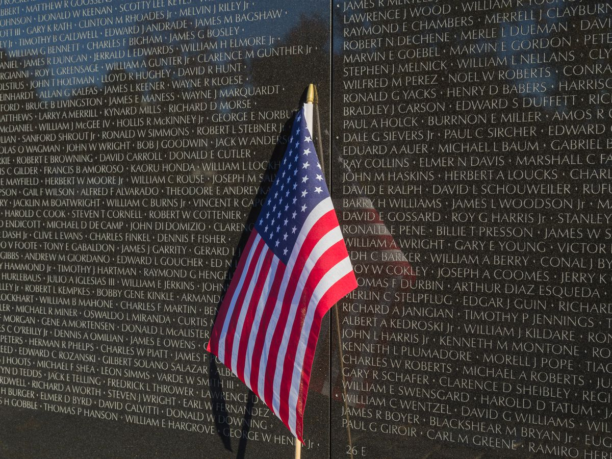 An American flag at the base of a memorial depicting thousands of names.