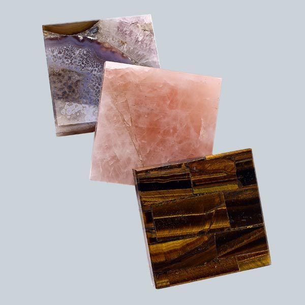 Three textured quartz blocks in purple, pink, and brown.