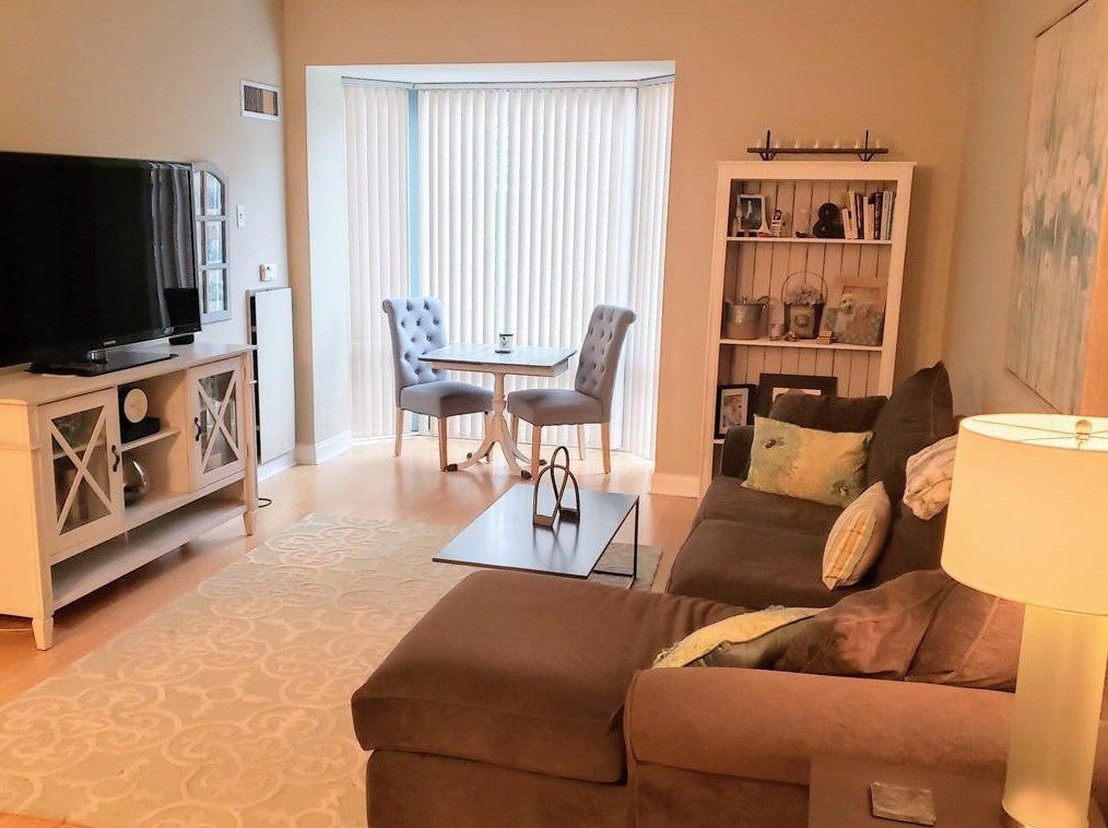 A living room with a seating area and a table and chairs arranged around a TV.