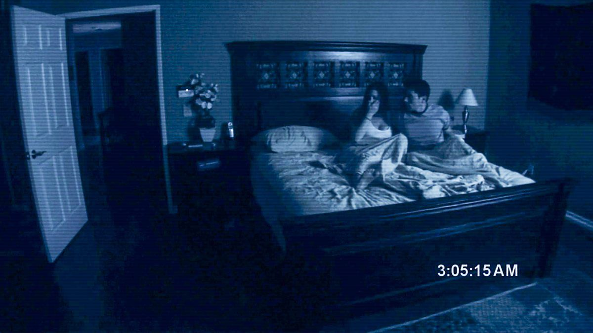A couple cowers in bed, looking at an open door