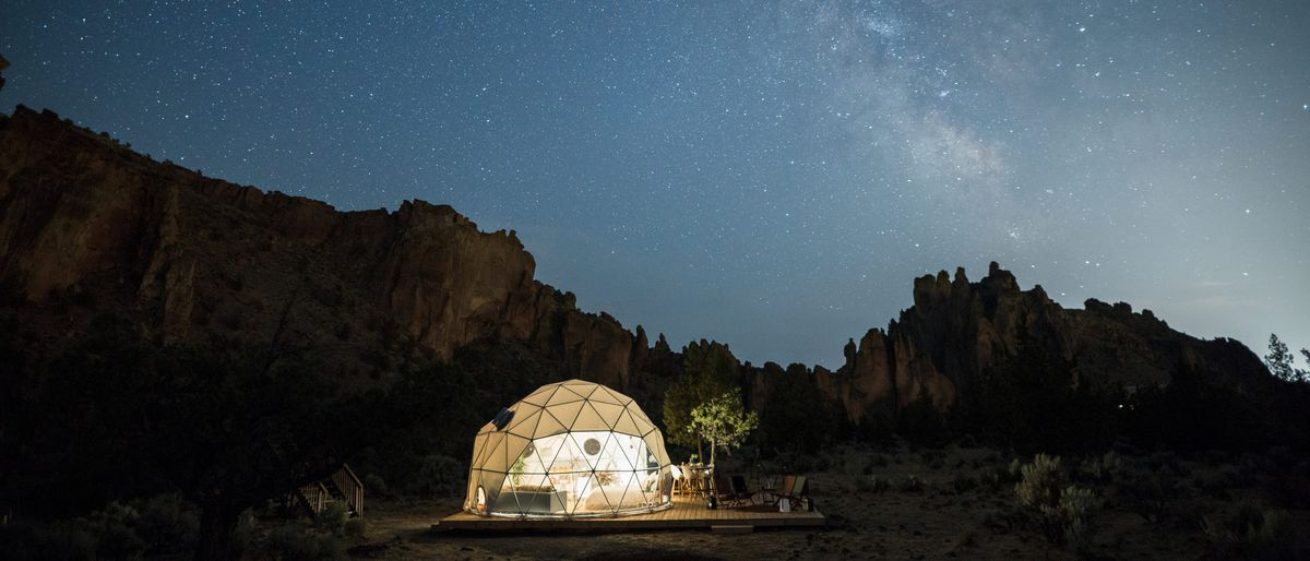 A tent lit up at night under a starry sky