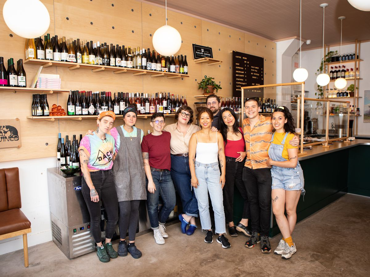 Nine people stand smiling at a camera, positioned in front of a counter and wine refrigerator in a restaurant with a light wooden wall behind