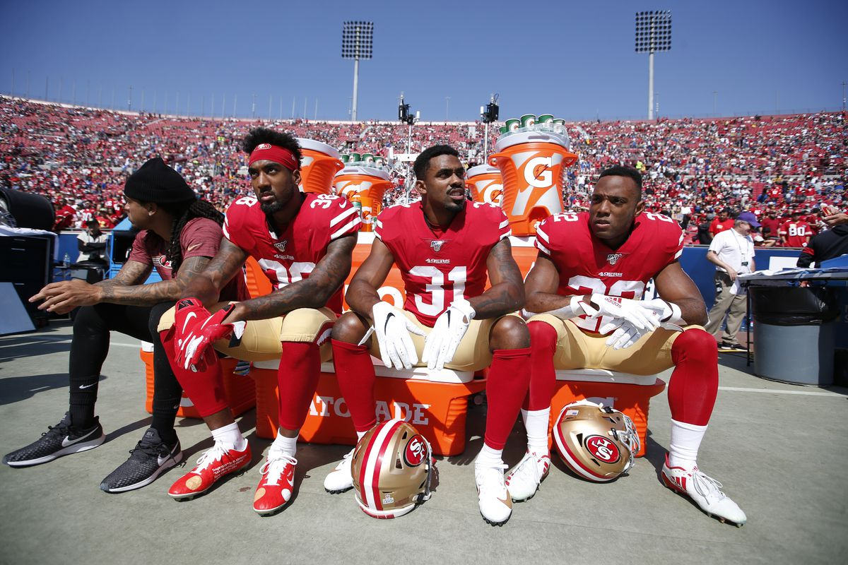 Antone Exum Jr., Raheem Mostert and Matt Breida of the San Francisco 49ers sit on the sideline prior to the game against the Los Angeles Rams at the Los Angeles Memorial Coliseum on October 13, 2019 in Los Angeles, California.