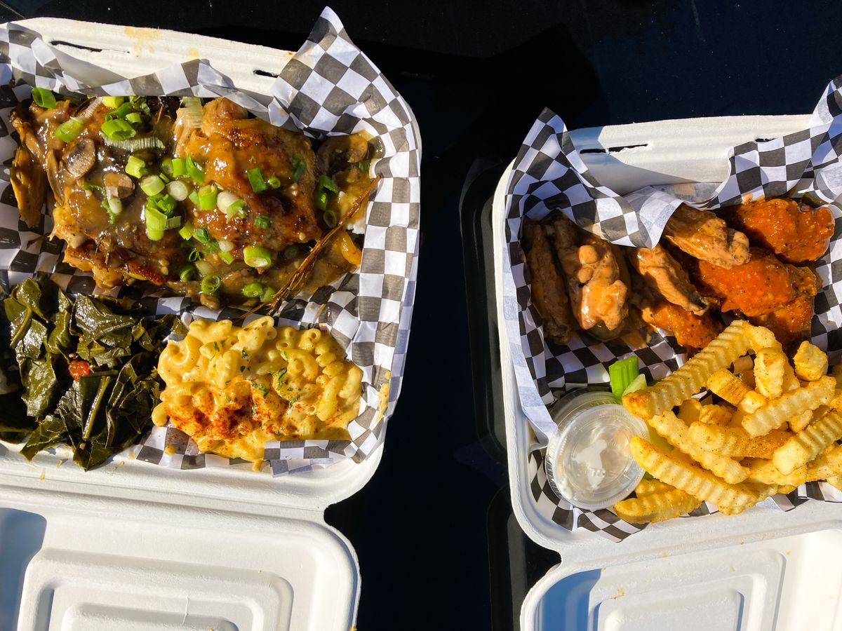 Two takeout boxes sit on the hood of a car, filled with chicken in a mushroom gravy, mac and cheese, collard greens, and red-hued wings.