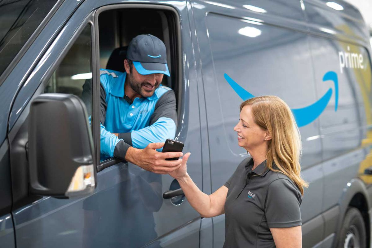 Amazon delivery people chat in front of a new Amazon delivery van