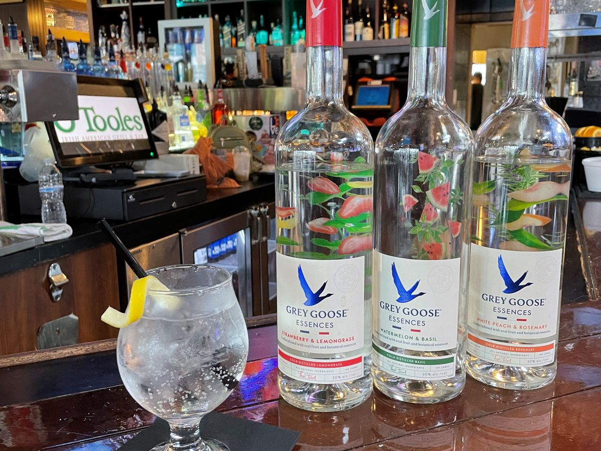 Three Grey Goose Essences liquor bottles on a bar with a clear spritz drink topped with lemon peel