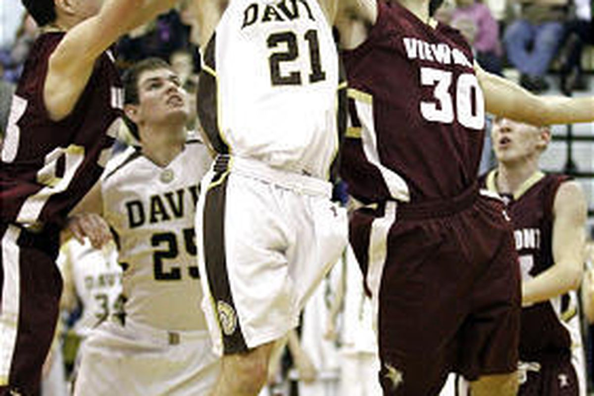Viewmont's Blake Wilkinson, left, and Eric North, right, surround Trevor Webb of  Davis in a battle for the ball.