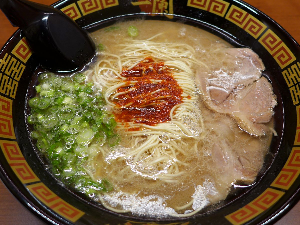 The classic milky pork bone broth is seen, with some shredded red ginger on top.