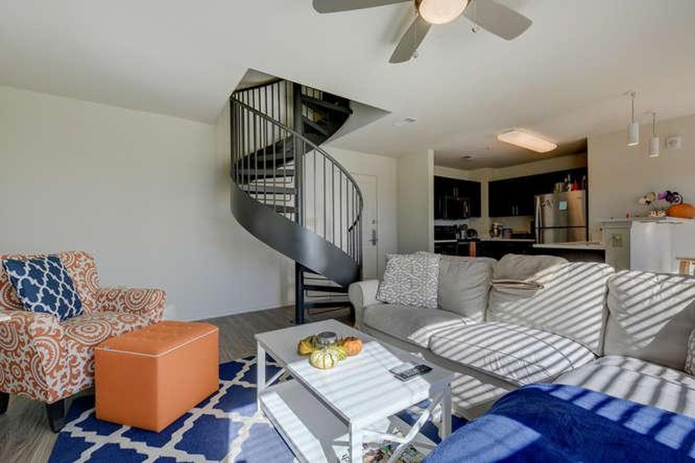 Bright living room with white walls, blue rug, spiral staircase