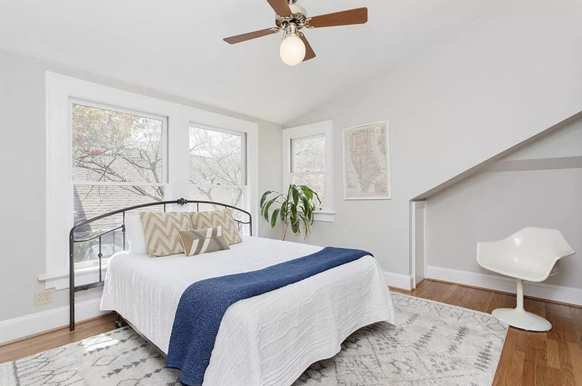 Bedroom with bed, chair, area rug, and picture windows.