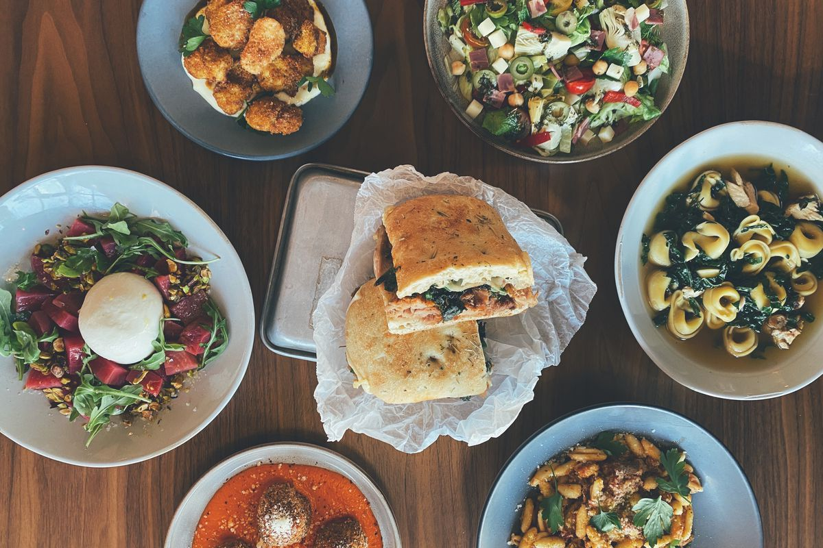 Pasta, burrata, meatballs, and sandwiches sit atop a wooden table