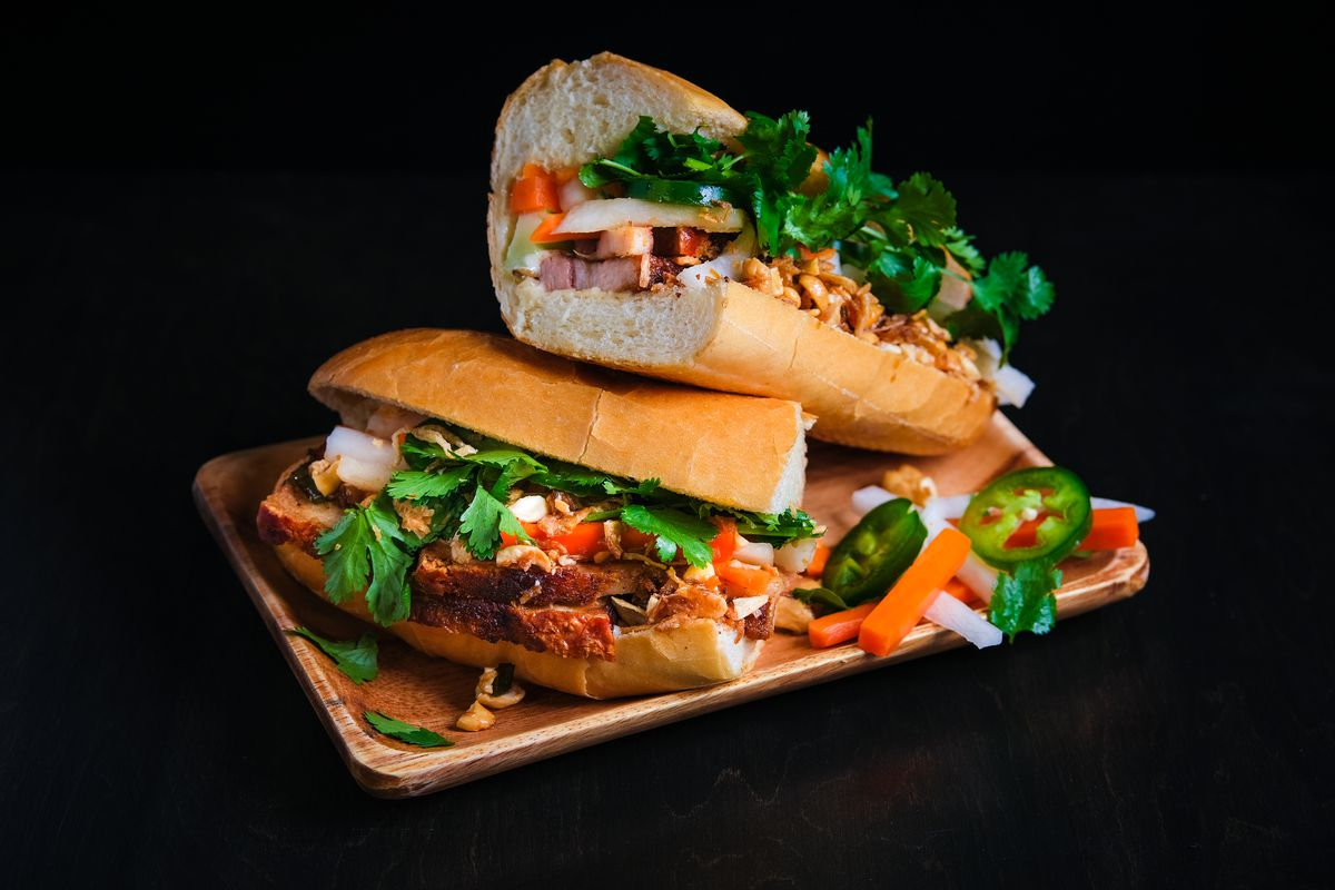 A picture of a large banh mi with pork belly, cilantro, and pickled veggies at Banh Mi Up