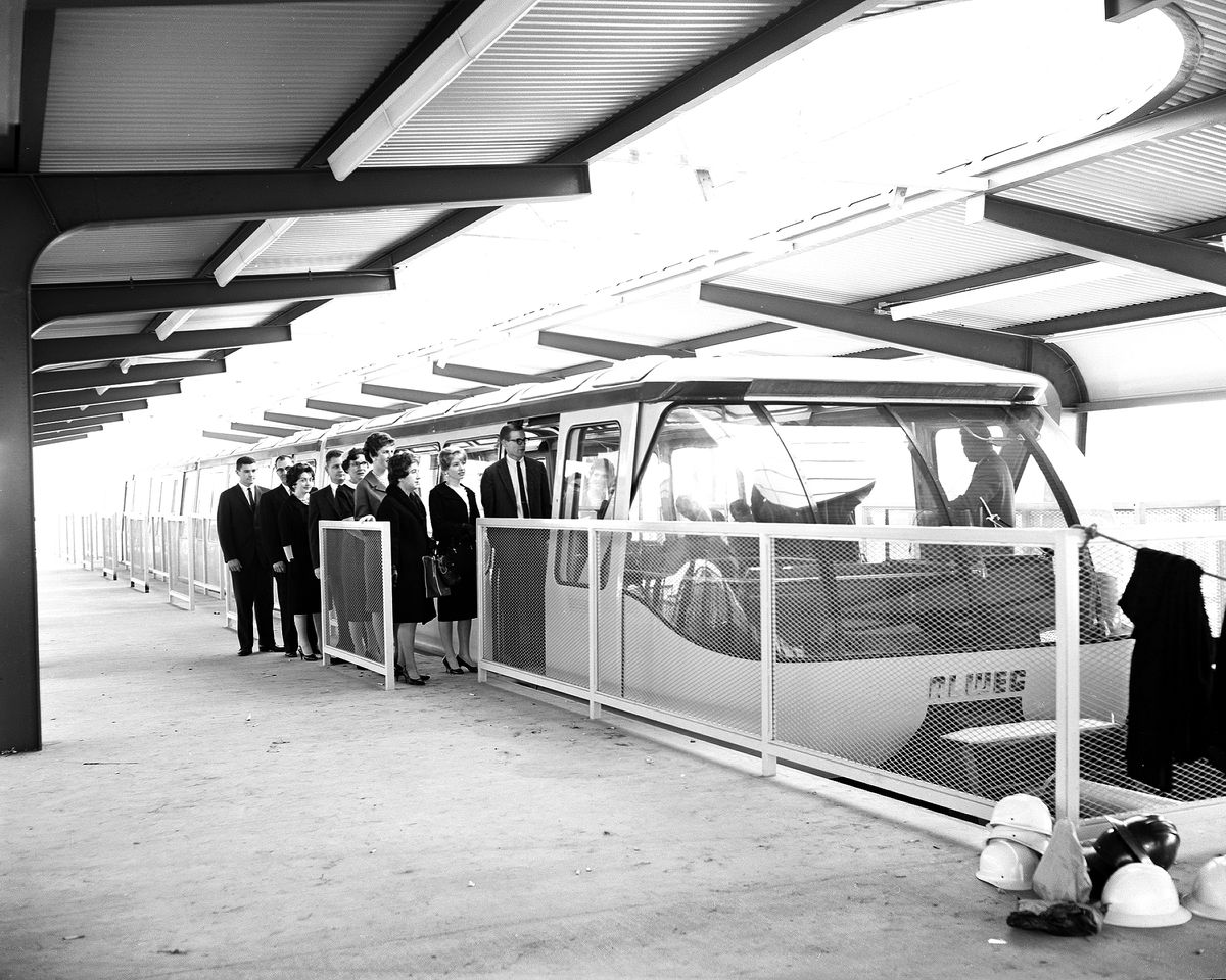 A group boards the monorail in a vintage, black and white photo