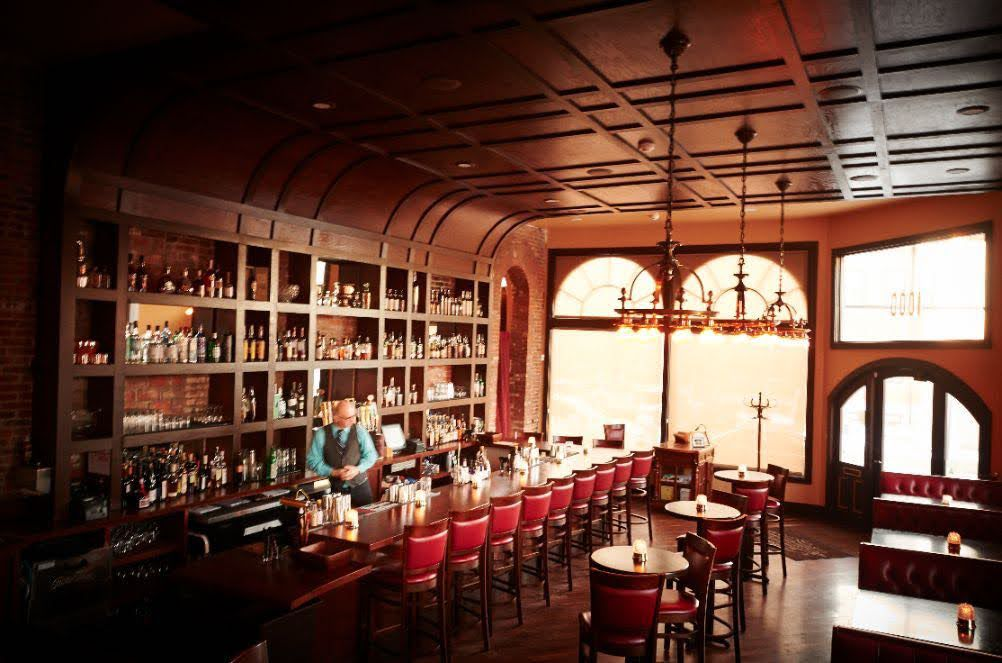 A bartender works behind a wooden bar in a wood paneled room, with large windows, red leather stools, tables and booths