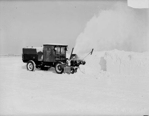 Image of a snow plow truck with a blower, clearing snow from a large, flat area inChicago,Illinois.
