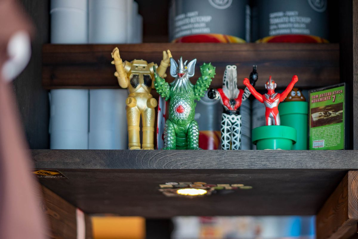 A collection of small Japanese figurines on a shelf at Taku.