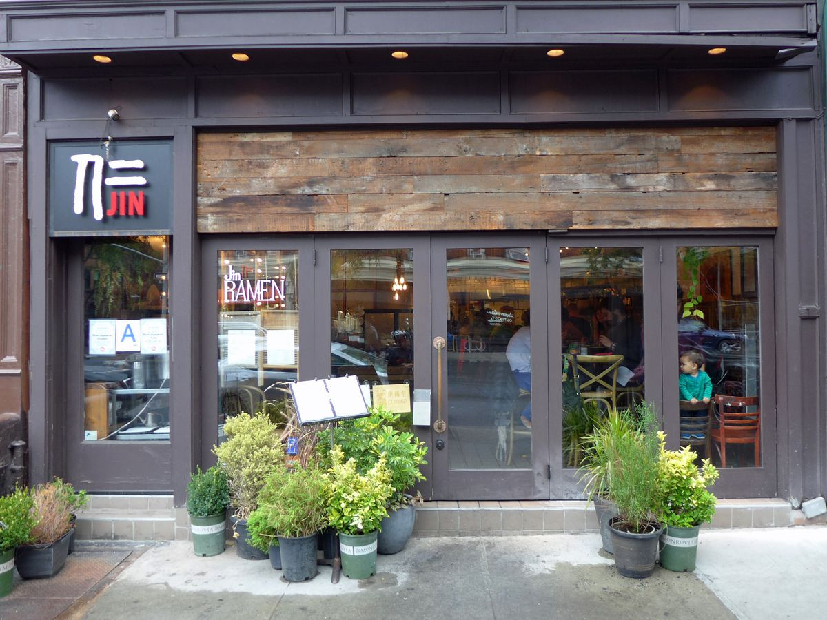 Jin Ramen storefront with two bushes in front.