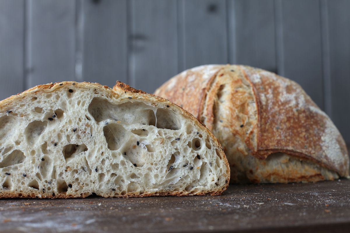 A cross-section of a loaf of sourdough bread sits in front of a downturned half of a loaf on a dark wood countertop