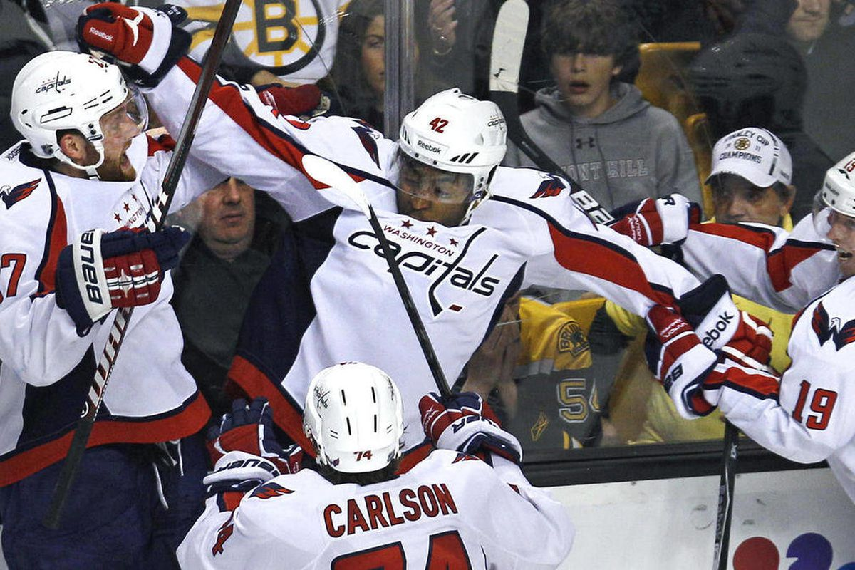 Washington Capitals right wing Joel Ward, center, is congratulated by teammates after his game-winning goal against the Boston Bruins during overtime of Game 7 of an NHL hockey Stanley Cup first-round playoff series in Boston, Wednesday, April 25, 2012. T