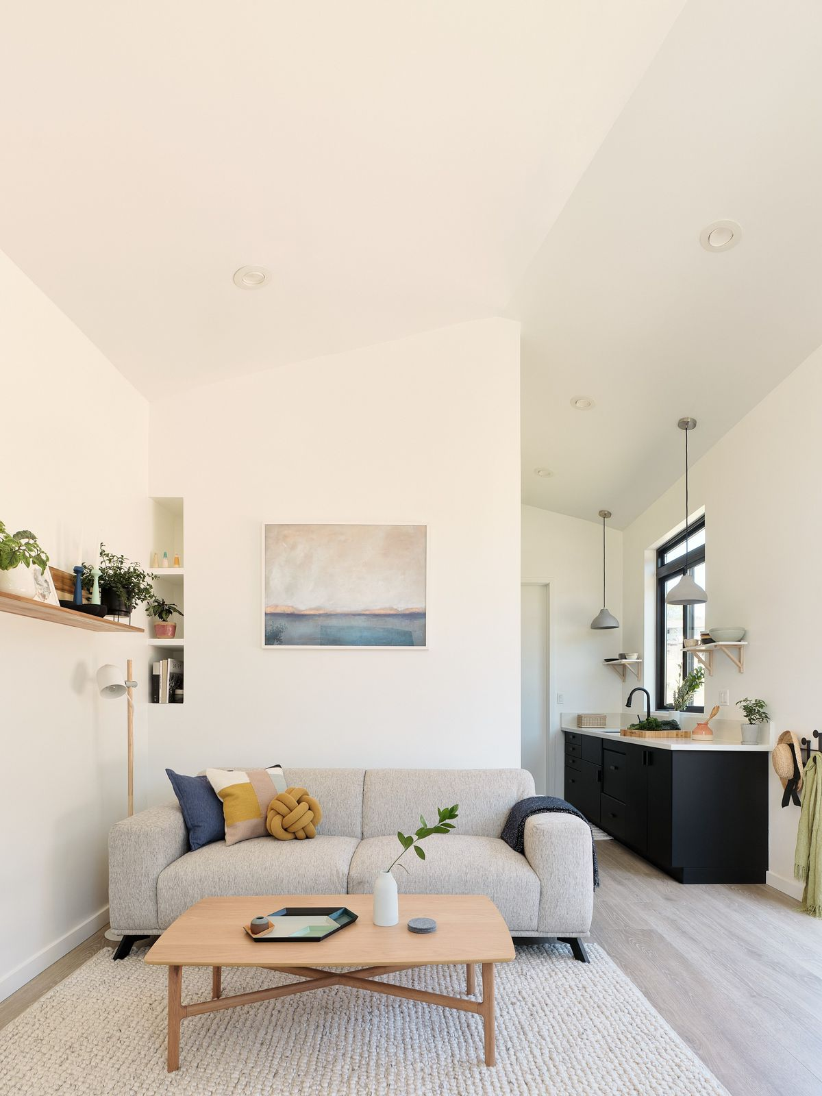 An airy living room has heigh ceilings, a gray two-seater sofa, pale wood coffee table, and a view of the kitchen area in one corner.
