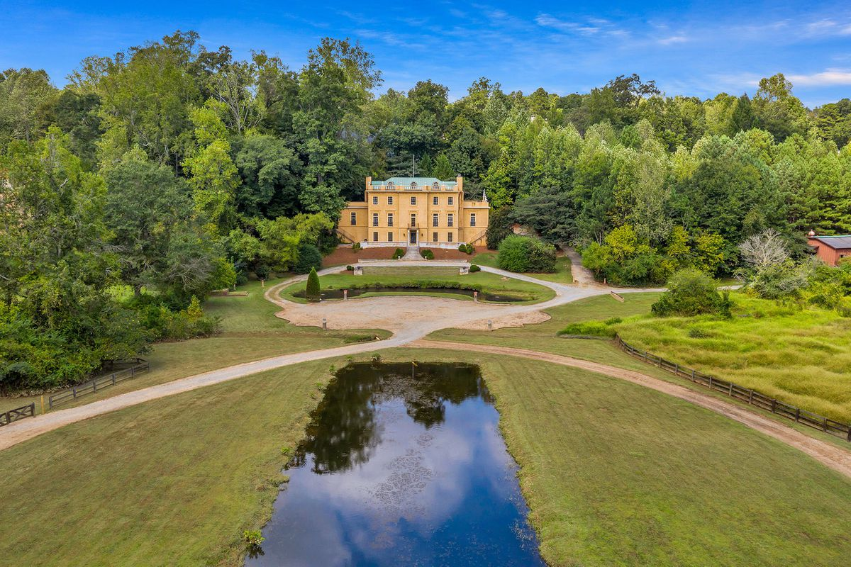 A yellow European-style mansion set atop a hill overlooking a pond with green grass all around.