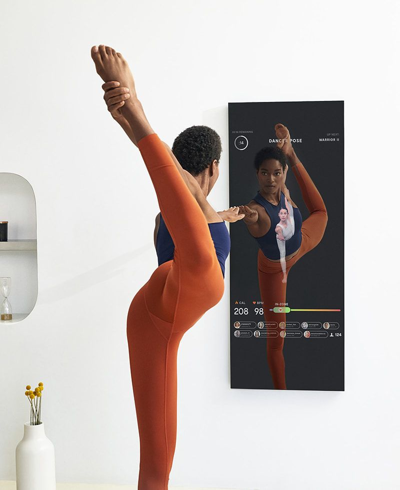 一个女人在镜子前做瑜伽动作时把腿放在身后。