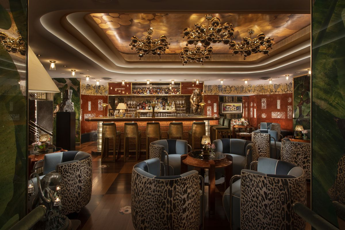An opulent bar with navy and leopard print velvet chairs