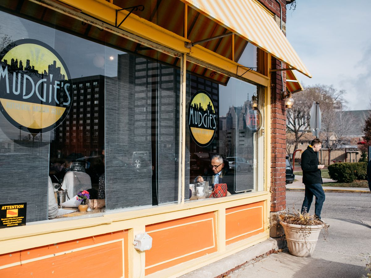 The exterior of Mudgie's on a sunny day. The building is painted orange with yellow awnings.